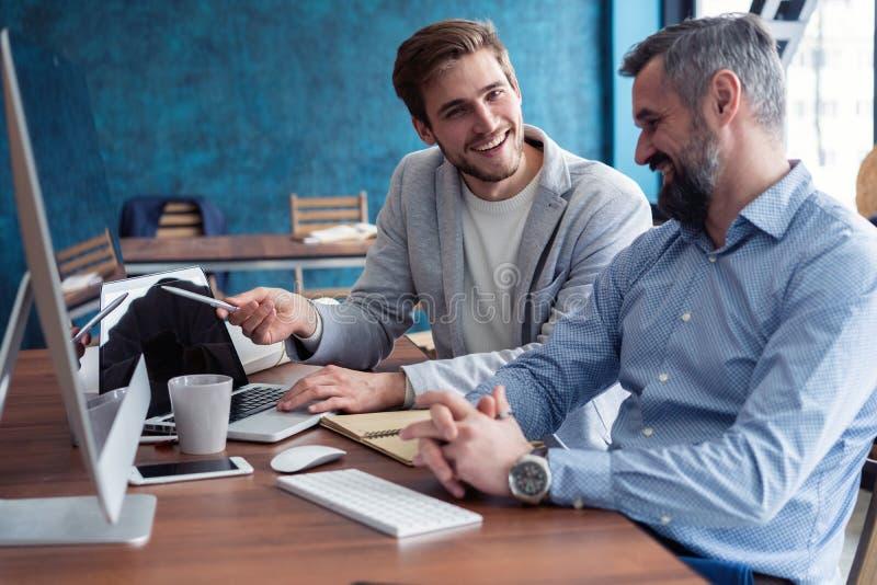 工作在他们的办公室的射击两个企业同事使用一台台式计算机 坐在他的有男性的书桌的人 库存图片