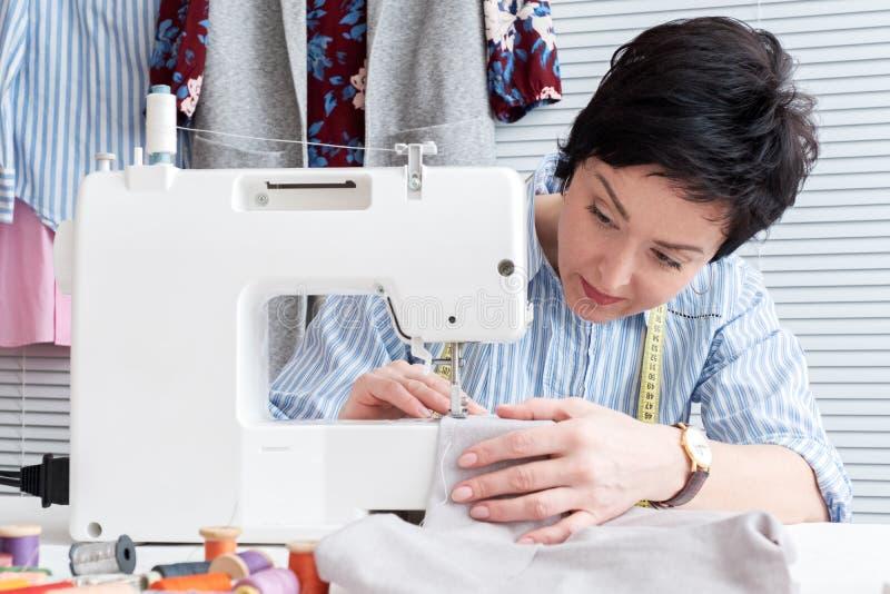 工作在有电子工业缝纫机的裁缝商店的裁缝 库存图片