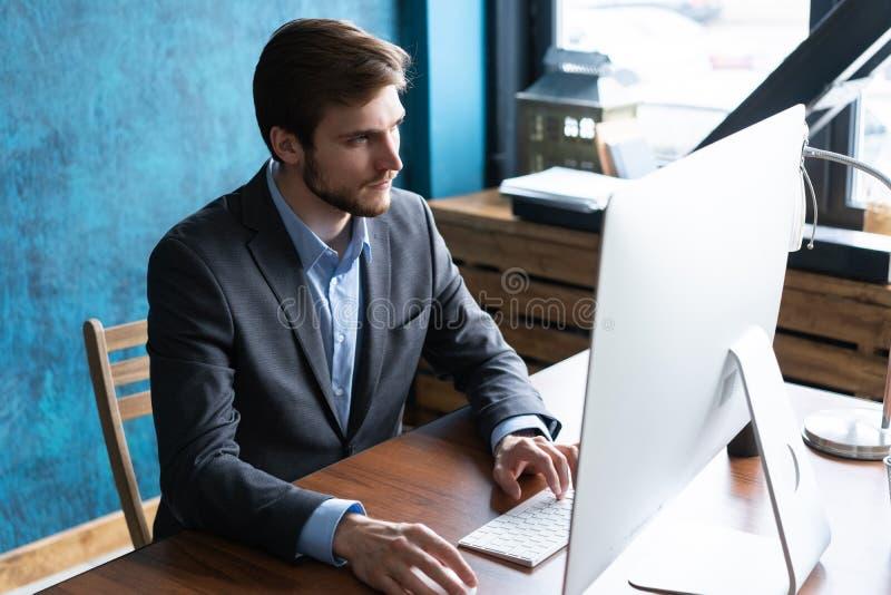 工作在计算机的人在当代办公室 免版税库存照片