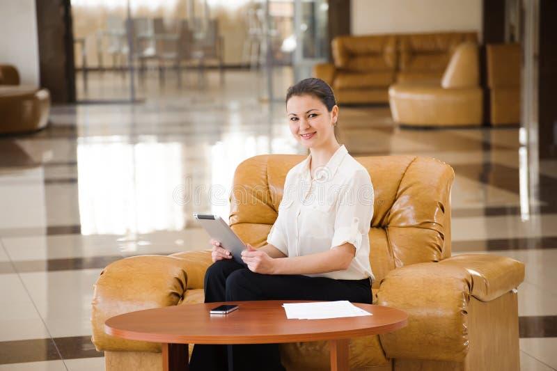 工作在ipad的繁忙的女商人画象,当坐在沙发时 3d商业查出的小的白色 免版税库存照片