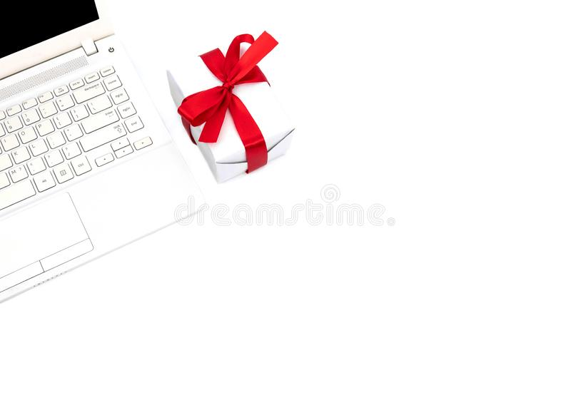 工作区顶视图关闭反对白色礼物盒在白色背景隔绝的蝶形领结红色丝带和笔记本电脑快活 库存图片