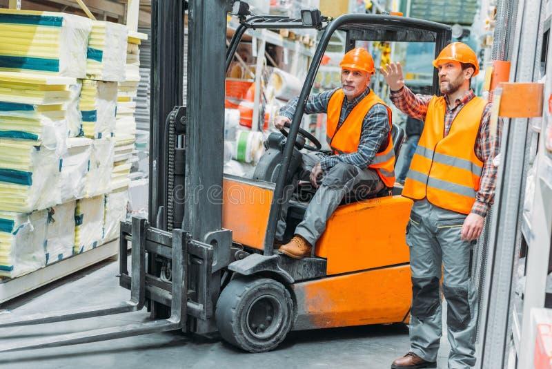 工作者和他的资深同事与铲车机器一起使用 免版税库存图片