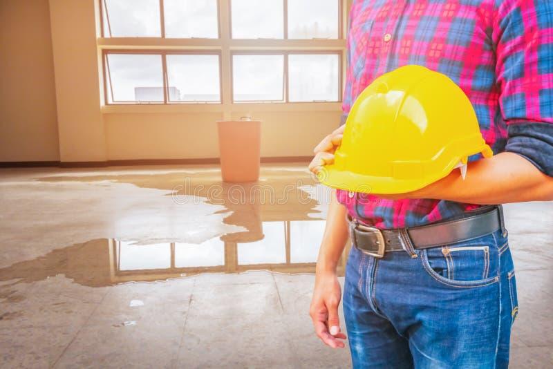 工程师藏品黄色安全帽塑料和水泄漏下落内部办公室背景 库存照片