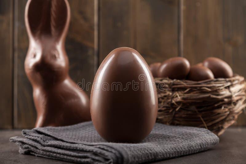 巧克力复活节兔子、鸡蛋和甜点在土气背景 免版税图库摄影