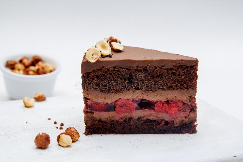 巧克力蛋糕片断用樱桃和榛子在白色背景 在桌特写镜头的可口巧克力蛋糕 库存照片