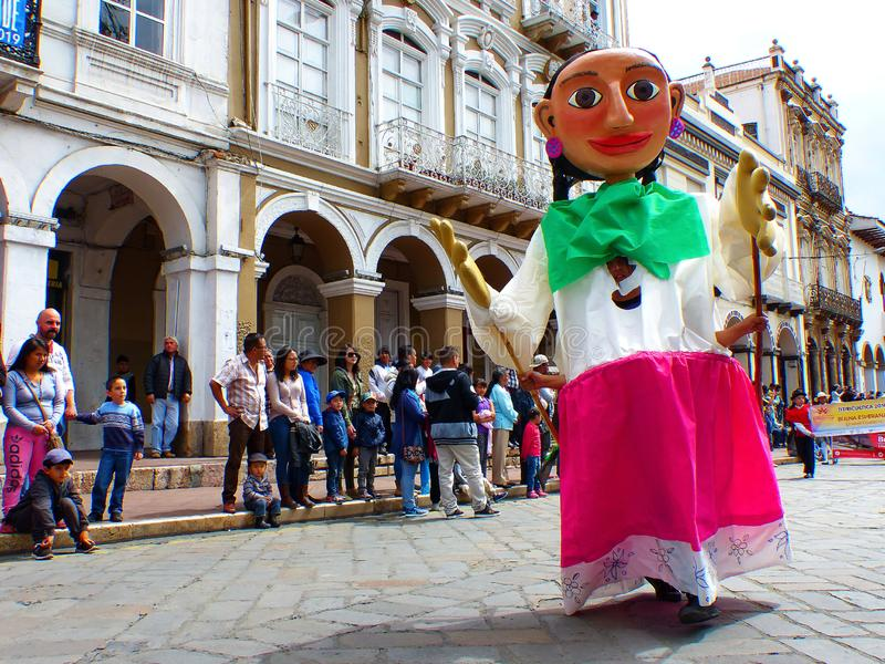 巨型五颜六色的时装模特当cuencana移动通过城市,昆卡省的历史中心 免版税库存图片
