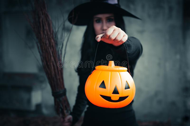 巫婆在手中食用在黑暗的背景,万圣节天概念的万圣节南瓜 库存照片
