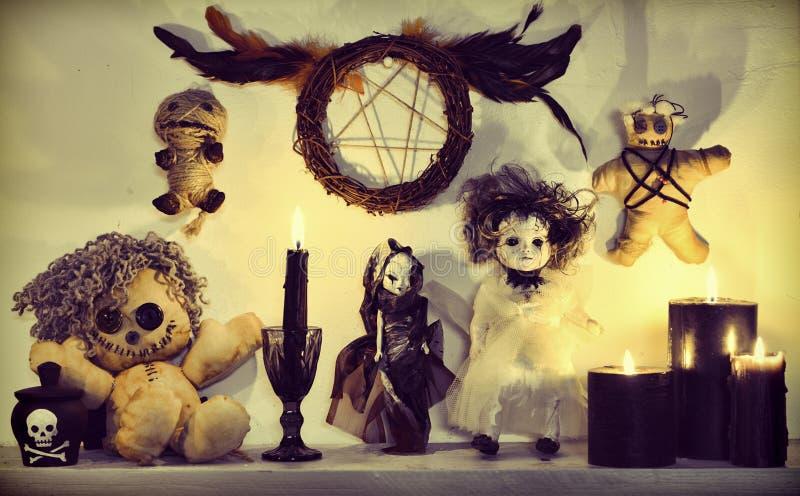 巫毒教与可怕玩偶、黑蜡烛和五角星形的仪式与羽毛 免版税库存照片