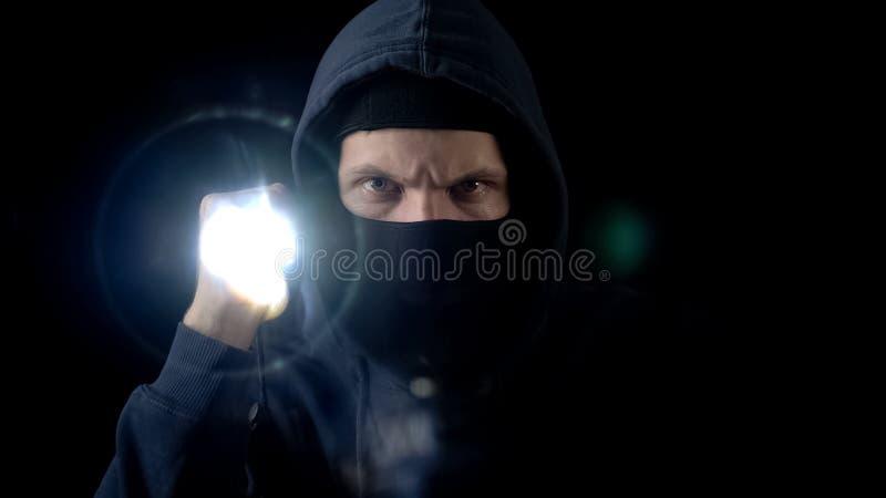 巴拉克拉法帽面具闪动的火炬的违法者,搜寻重要信息 免版税库存图片