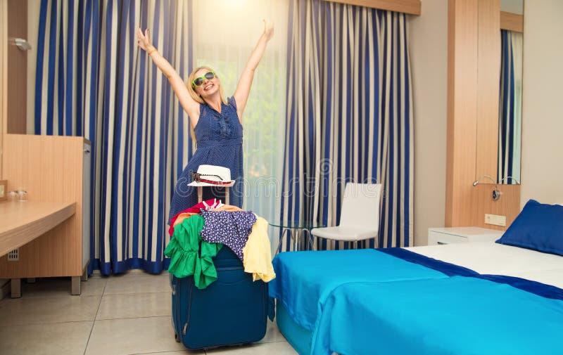 带着手提箱的年轻女人在酒店房间 在一次长的旅途以后的休息 免版税库存图片