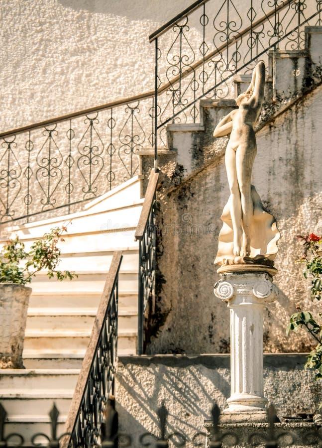 希腊房子的庭院的装饰有大理石步的和在Kefalonia,希腊海岛上的一个雕象  免版税库存图片