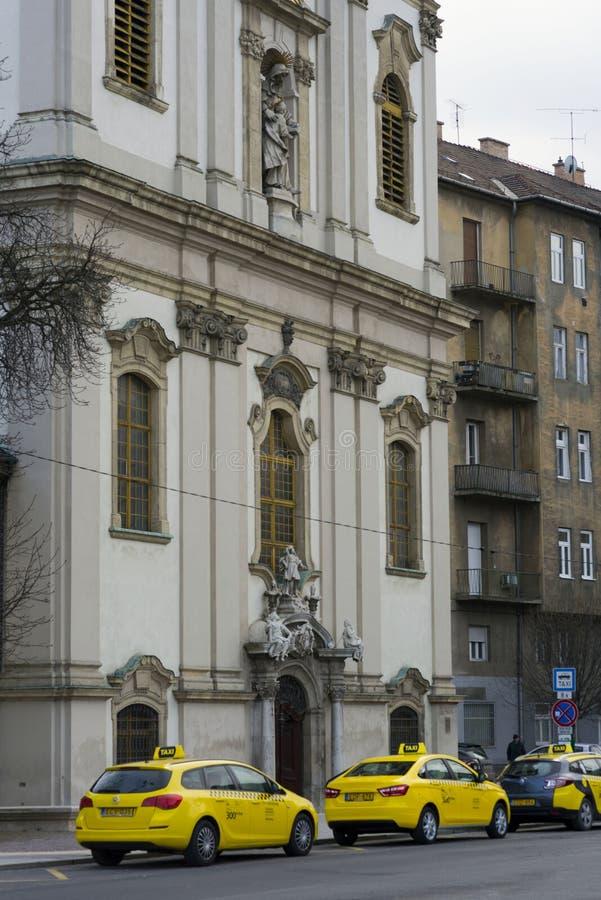 布达佩斯,匈牙利,2019年2月 黄色出租汽车在一个美丽的房子在布达佩斯,匈牙利的首都附近停放 免版税库存图片