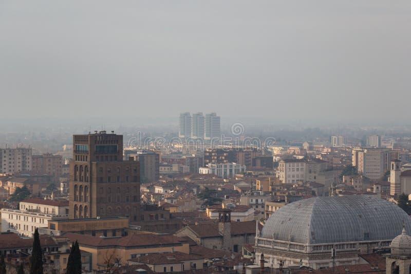 布雷西亚都市风景,在雾,伦巴第,意大利的大厦 库存图片