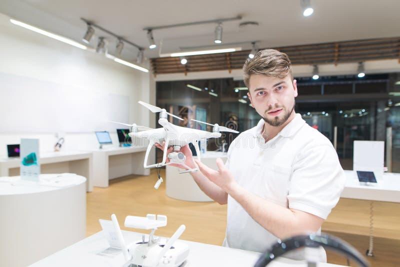 帅哥在他的手在一家现代商店和神色上站立与一quadcopter在照相机 库存照片