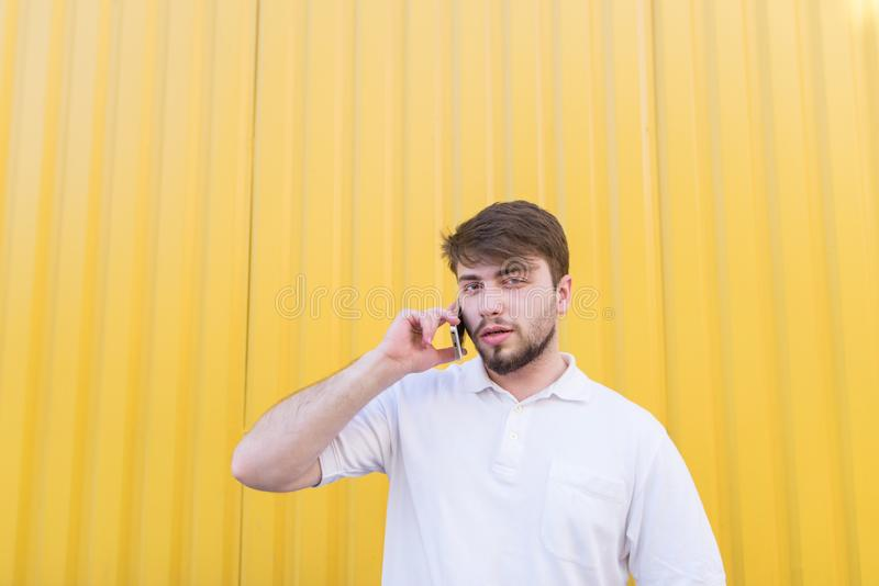 帅哥在色的墙壁的在电话的背景,谈话和神色站立在照相机 免版税图库摄影