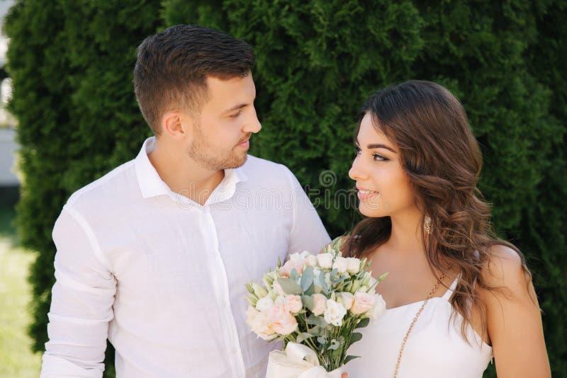 帅哥和美女白色衣裳的 结合走外面 花花束 图库摄影