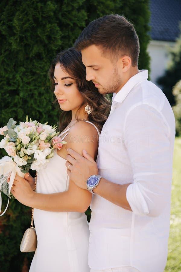 帅哥和美女白色衣裳的 结合走外面 花花束 库存图片