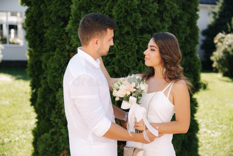 帅哥和美女白色衣裳的 结合走外面 花花束 库存照片