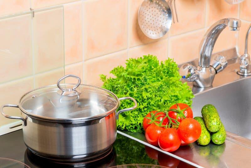 干净的菜和平底深锅在火炉在水槽附近在厨房里 免版税库存照片