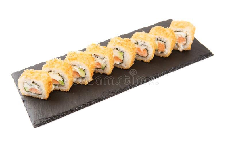 干酪奶油色深鳗鱼新油煎的于做maki外部滚三文鱼熏制的寿司蔬菜 新三文鱼外部 热的油煎的寿司 图库摄影