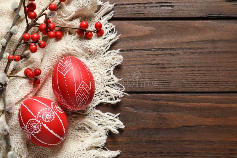 平的被放置的构成用在木桌上的被绘的红色复活节彩蛋 免版税库存照片