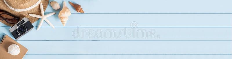 平的被放置的照片saeshell和帽子在蓝色木桌、顶视图和拷贝空间上蒙太奇的您的产品,夏天概念 免版税图库摄影