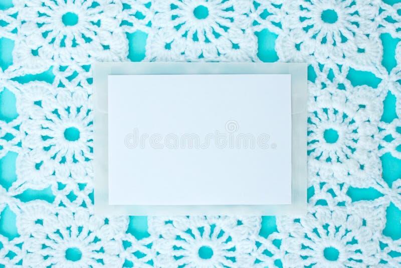 平,放置,纸片文本的在与钩针编织的白色葡萄酒鞋带的蓝色背景,冬天题材,方形的装饰品 库存照片