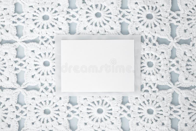 平,放置,纸片文本的在与钩针编织的白色葡萄酒鞋带的蓝色背景,冬天题材,方形的装饰品 免版税图库摄影