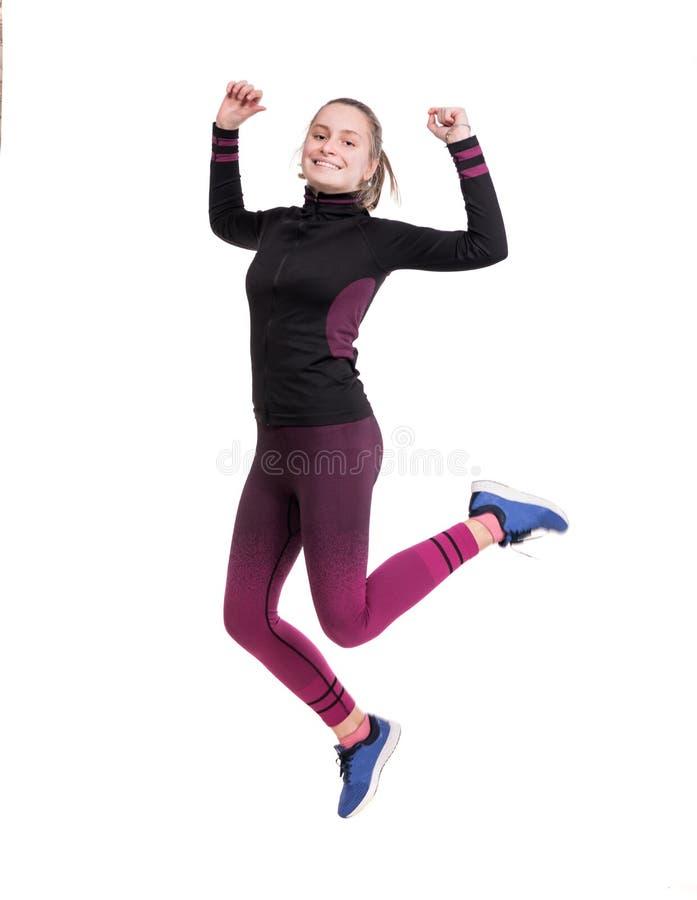 幸福、自由、行动和体育概念 跳跃在空气的微笑的青少年的女孩 免版税库存照片