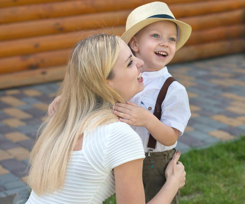 幸福家庭的生活片刻!小男孩体贴拥抱他的母亲 库存图片