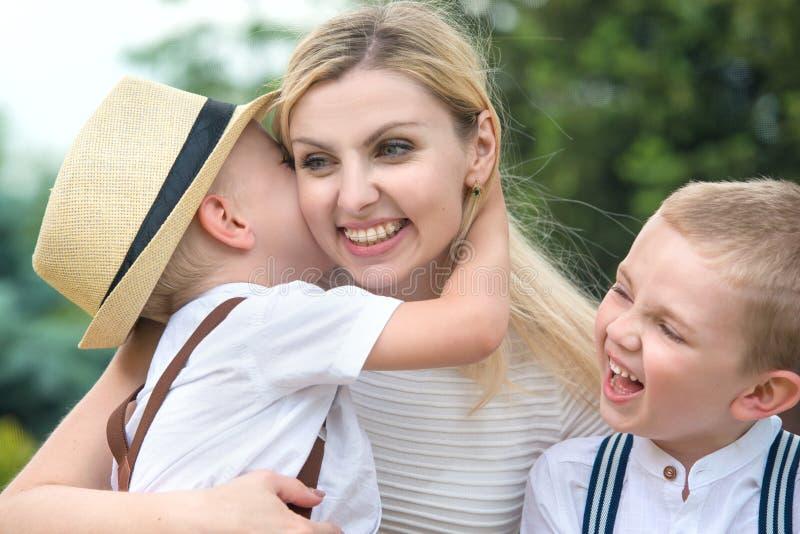 幸福家庭的生活片刻!年轻母亲和两个美丽的儿子 图库摄影