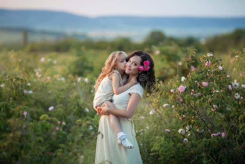 幸福家庭:有她的走在a的麦子橙色领域的小逗人喜爱的女儿的一年轻美丽的孕妇 免版税库存照片