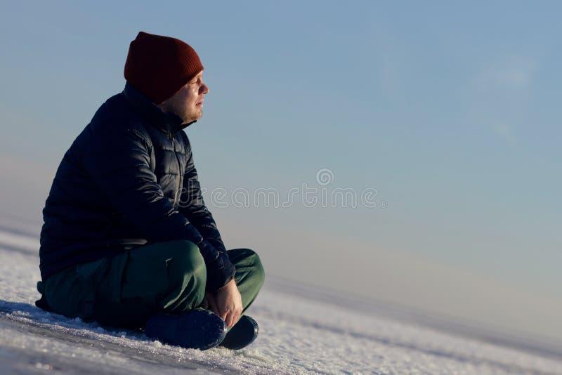 年轻人在冬天坐在雪和神色冰在太阳 免版税库存图片