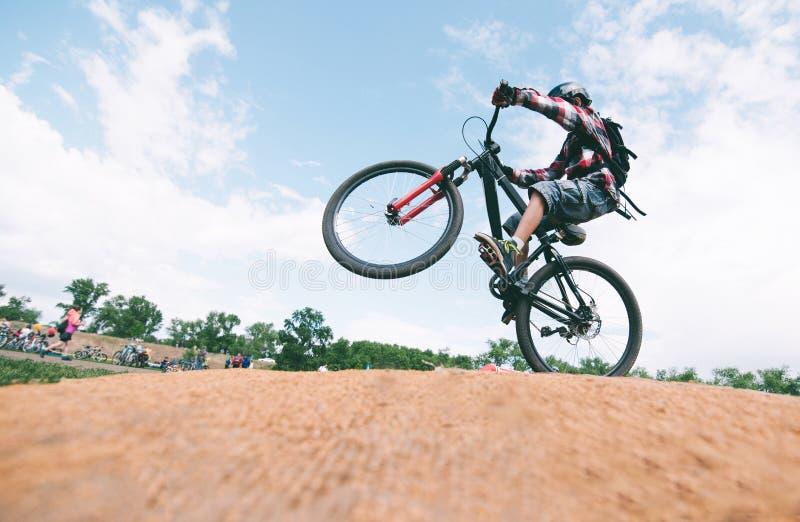 年轻人在登山车做把戏 骑自行车者在自行车跳 免版税库存图片