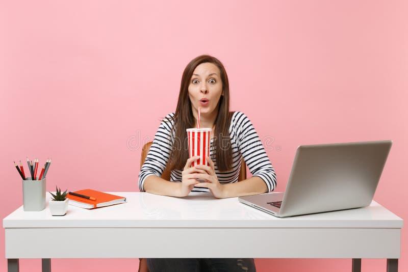 年轻人惊奇滑稽的妇女拿着plactic杯子用可乐的或苏打坐工作在有当代个人计算机膝上型计算机的白色书桌 图库摄影
