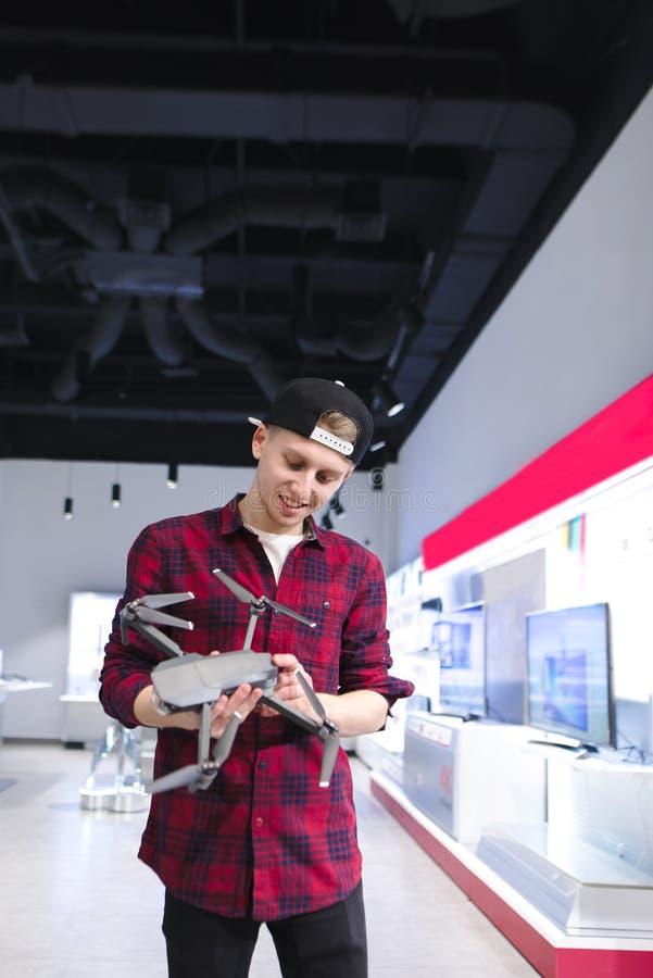 年轻人看一条寄生虫技术商店 在寄生虫商店买quadcopter 免版税图库摄影