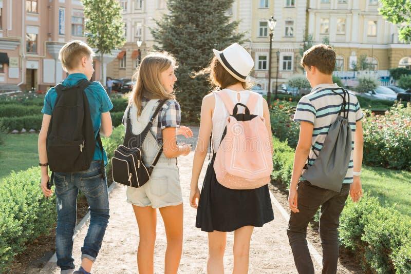 年轻人走在城市,谈话一个小组的朋友的少年微笑获得乐趣在城市,从后面的看法 库存图片