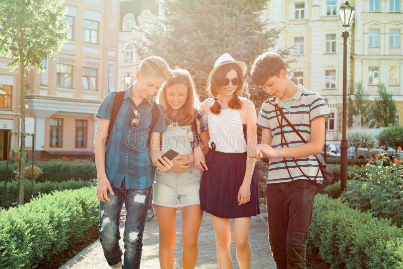 年轻人走在城市,谈话一个小组的朋友的少年微笑获得乐趣在城市 友谊和人们 库存图片