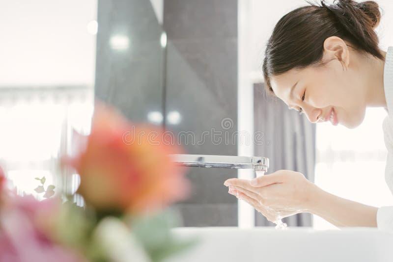 年轻亚洲人洗她的面孔的WWoman 免版税库存图片