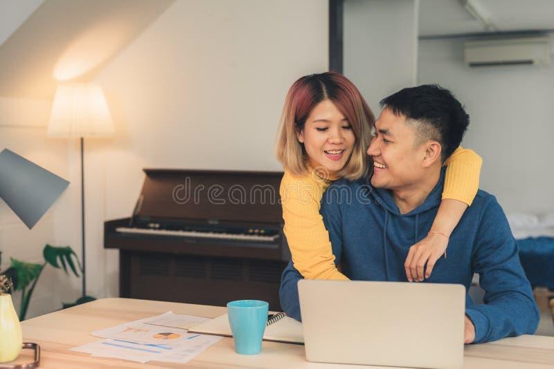 年轻亚洲夫妇处理的财务,回顾他们的银行帐户使用便携式计算机和计算器在现代家 妇女和 库存照片