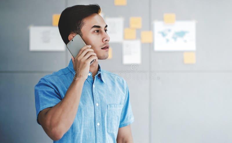 年轻亚洲商人工作在办公室候选会议地点和谈话通过智能手机 免版税库存照片