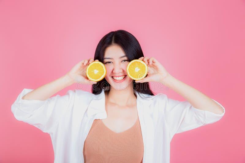 年轻亚裔妇女健康微笑的显示的桔子画象  免版税图库摄影
