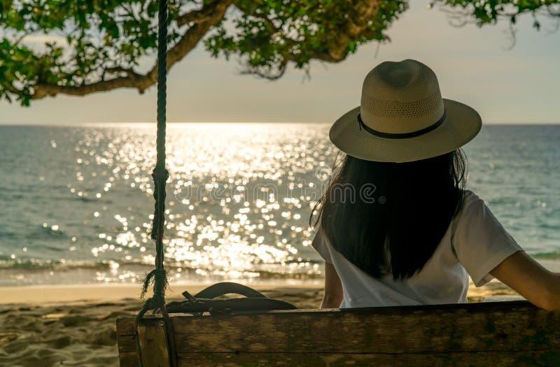 年轻亚裔妇女和放松坐摇摆在海边在度假暑假 夏天震动 单独妇女旅行在度假 底板 免版税库存照片