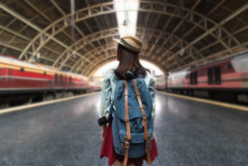 年轻亚裔在火车站的背包徒步旅行者女性身分后面看法  旅行生活方式概念 免版税库存图片