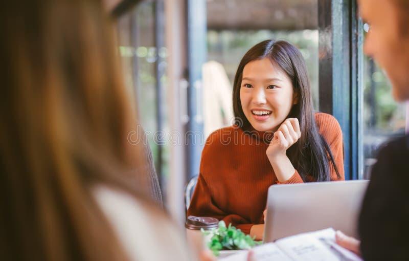 年轻亚裔的女孩聊天和使用膝上型计算机的朋友在咖啡馆在咖啡馆咖啡馆在笑的大学一起谈话和 库存照片