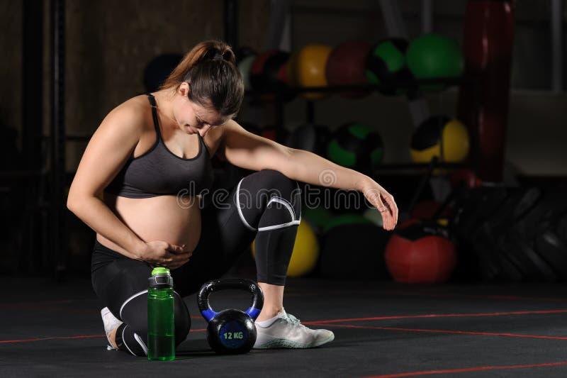 年轻从塑料瓶的孕妇饮用的wate在健身房 免版税库存照片