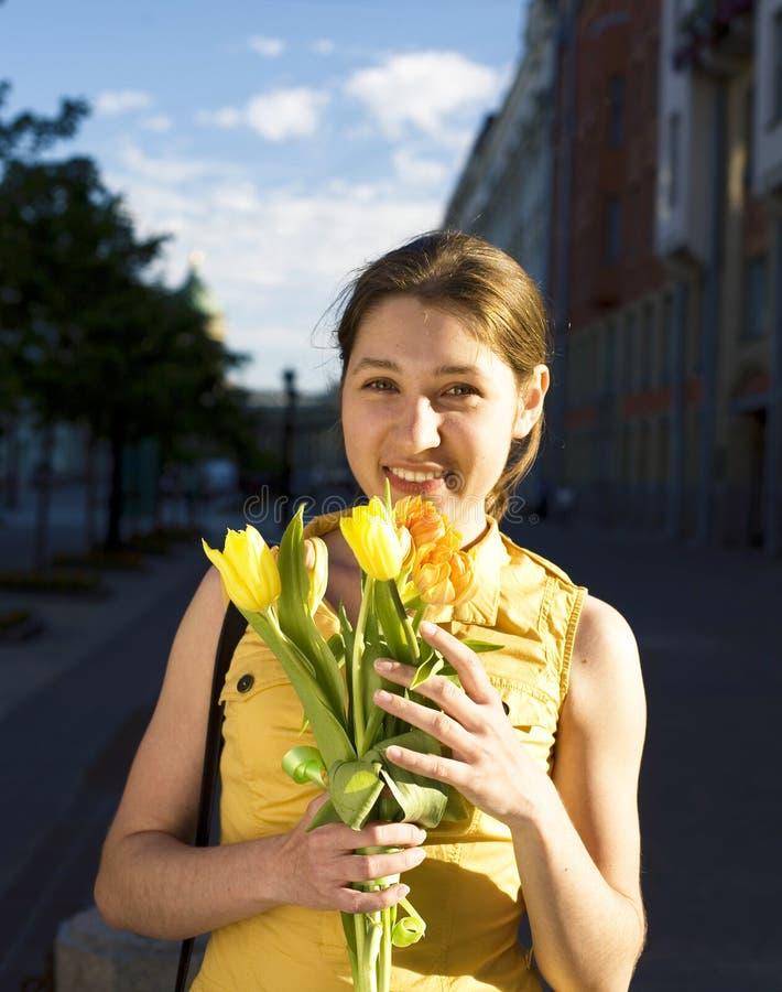 年轻俏丽的女孩在城市室外与花,生活方式人概念 免版税库存图片