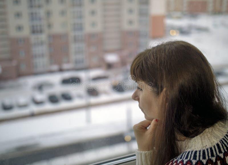 年轻俏丽的妇女看起来哀伤窗口对街道外面,被弄脏的背景 免版税库存图片