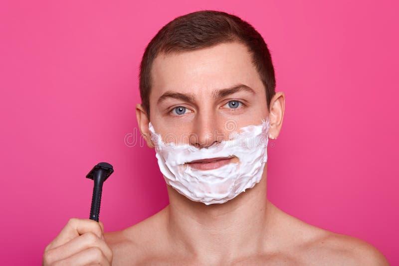 年轻可爱的人准备好刮与剃刀在卫生间,在面孔上把奶油放,在桃红色背景 有泡沫的帅哥 库存照片