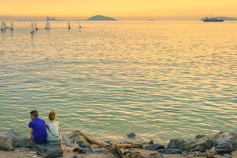 年轻夫妇后面看法一起坐在享受日落的海洋前面的石头 图库摄影